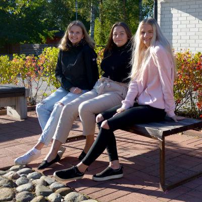 Tre unga kvinnor sitter på en bänk framför en skolbyggnad.