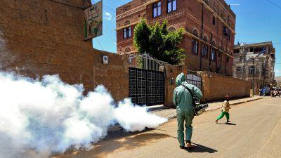 En medlem av den statliga jemenitiska insatsstyrkan mot virusspridningen sprutar desinfektionsmedel på en gata i huvudstaden Sanaa.