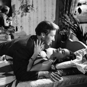 Pertti Weckström ja Eila Peitsalo syleilevät sängyllä elokuvassa Poika eli kesäänsä.