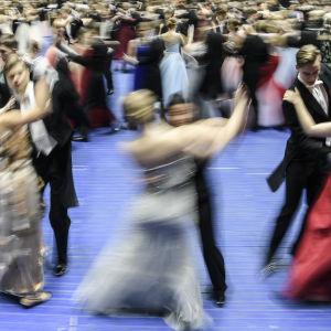 Dansande par virvlar förbi på ett blått golv.
