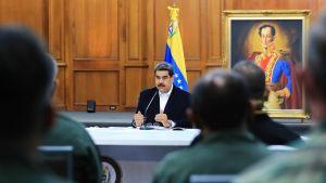 presidentti Maduro pöytänsä ääressä, edessä miesten hahmoja