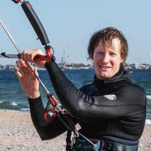 Man i våtdräkt står på en sandstrand i solskenet och håller i en segeltrapets som är fäst runt hans midja med en sele.