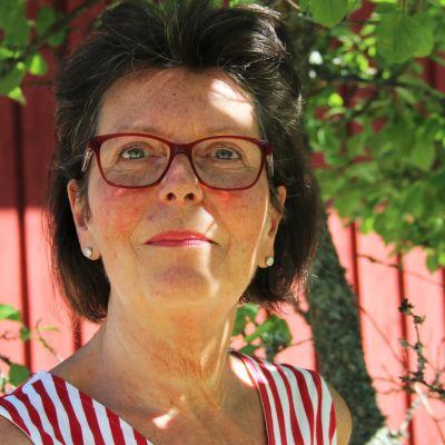 En kvinna med mörkt hår, glasögon med röda bågar och röd-vit (polka) randig topp i en lummig trädgård med rött trästaket, träd och sol