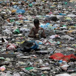 En pojke i New Delhi står med avfall upp till midjan och söker efter saker som kan återanvändas.
