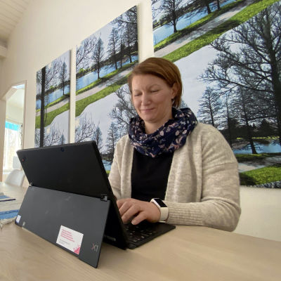 Nainen tekee tietokoneella etätöitä kotonaan