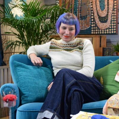 En kvinna som sitter i en soffa. Kvinnan är textilexperten Leili Mänder som jobbar med att sprida kunskap om textilvård och hållbarhet och som driver kontot @lagningsaktivisterna på Instagram.