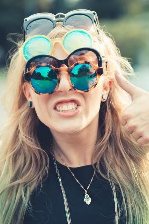 En kvinna med blont hår fotograferad i närbild med flera par solglasögon på huvudet. Hon visar tummen upp.