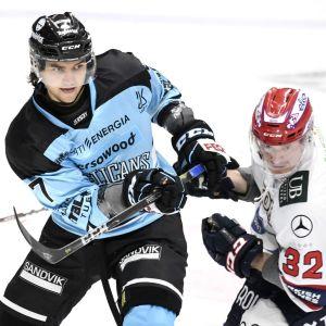 En blåklädd och en vitklädd hockeyspelare i närkamp.