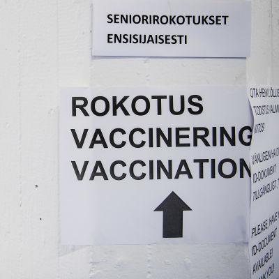 Skylt bland annat med texten vaccinering och till vänster en kvinna som bär munskydd. 85-åringar och äldre samt närvårdare vaccinerades på Busholmen i Helsingfors den 1 februari  2021.
