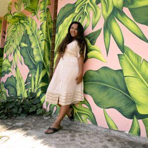Kuvassa Away - Ayu poseeraa hymyillen värikkään seinän edessä Balilla.