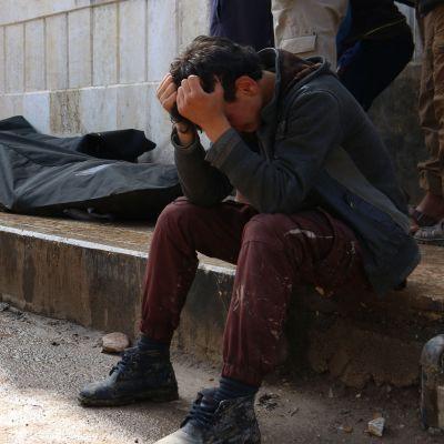 En syrisk man gråter intill tre liksäckar i rebellhållna Azaz, norra Syrien, efter ett bombdåd 3.5.2017