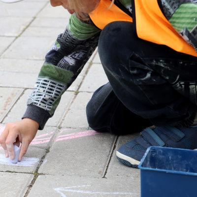 Lapsi piirtää liiduilla kivetykseen
