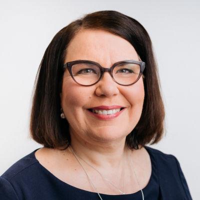 Merja Ylä-Anttila. Tummahiuksinen, silmälasipäinen nainen