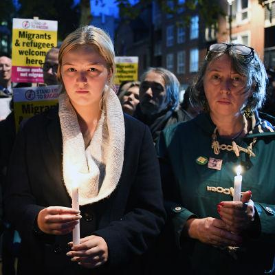 Personer håller i ljus och demonstrerar för flyktingar i London.