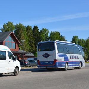 En större taxi och en buss står parkerade vid en affärsfastighet i rött trä.