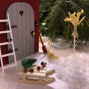 Ett miniatyrlandskap med en tomtenissedörr, snö och småfåglar, en kälke, stege och havrekärvar.