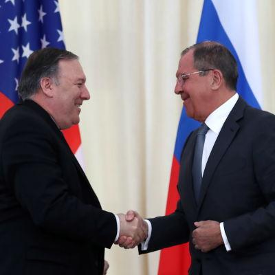 Två män skakar hand framför amerikansk och rysk flagga.