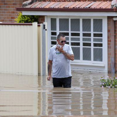En man utanför sitt översvämmade hus i Bundaberg
