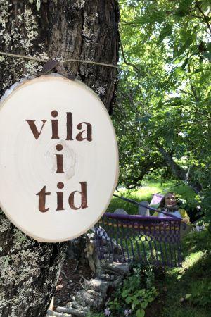 """Tavla med texten """"vila i tid"""" hänger på ett träd. I bakgrunden en kvinna som ligger i en hängmatta.r"""