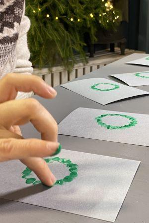 Fingerfärgstryckning med grön färg på grå kartong