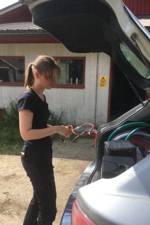 Kandit-ohjelman eläinlääkärikandi Veera ottamassa tarvikkeita auton peräkontista