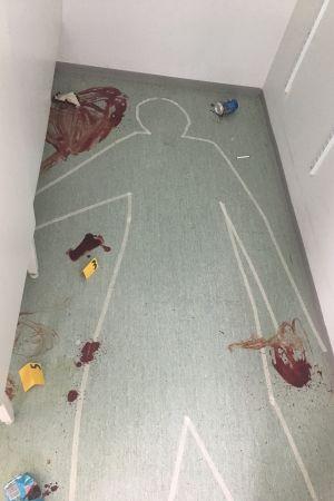 Konturerna av en människa är ritade med tejp på ett golv med blod och andra ledtrådar.