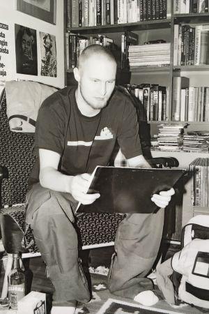 Svartvit bild på Palface som ung sittande på stol i arbetsrum med en tavla eller häfte i handen som han studerar.