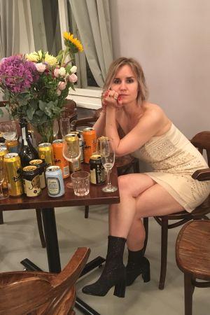 Nainen istuu juhlavaatteissa ja hänen edessään pöydällä on paljon pulloja ja tölkkejä