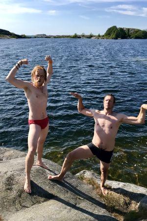 Juontajat Tom Nylund ja Mikko Peltola pullistelevat rantakivillä.