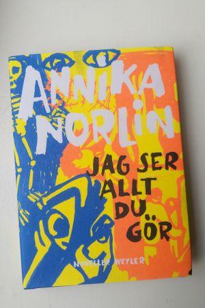 """Bild på pärmen av Annika Norlins novellsamling """"Jag ser allt du gör"""" som går i orange, blått och gult."""