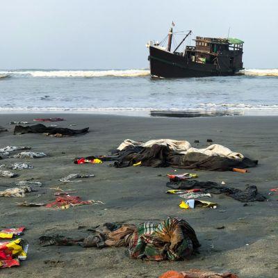 En del av de räddade rohingyernas ägodelar låg kvar på stranden nära Teknaf på torsdag morgon. Det är oklart om trålaren i bakdrunden är den båt som de drivit omkring på i nästan två månader.