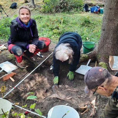 Två personer gräver i en grop, en tredje sitter på huk vid kanten av gropen. Det är en kvinna som tittar in i kameran och ler.