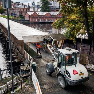 Kauhalla varustettu traktori nostaa sillan kattorakennetta pois purettavasta sillasta.