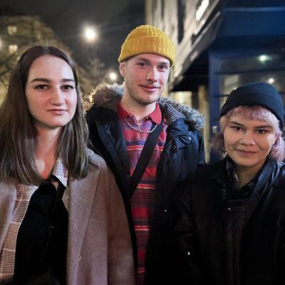 Tre ungdomar står ute på en gata på natten. De ser bestämt in i kameran.