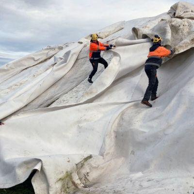 Levi Ski Resortin työntekijät purkavat viiroja säiölumikinosten päältä.
