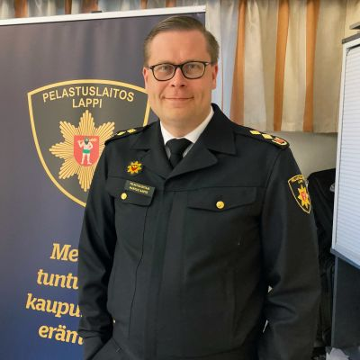 Lapin pelastuslaitoksen pelastusjohtaja Markus Aarto palomiehen univormussaan, taustalla Lapin pelastuslaitoksen mainosroll-up.