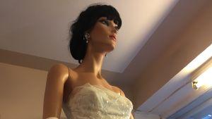 En modedocka med mörkt hår och i klädd en vit klänning.
