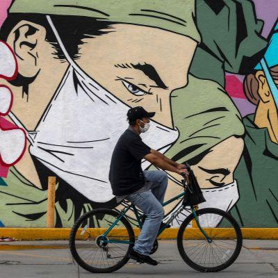 En person med ansiktsskydd på cyklar. I bakgrunden syns en vägg som är täckt med ett stort konstverk av personer med ansiktsskydd på.