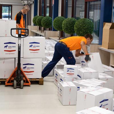 Työntekijät lastaavat postimyynnin laatikoita lavalle Laplandia marketissa Lappeenrannan Nuijamaalla.