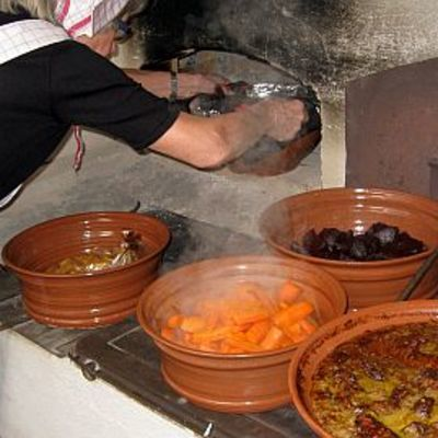 Nainen ottaa ruokaa leivinuunista, ruoka höyryää savipadoissa