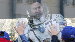 Nick Hague vinkar av barn inför starten mot ISS den 11.10.2018