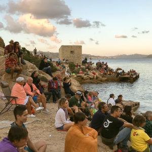 Konserttiyleisö istuu Italiassa merenrannan kivillä ilta-valossa.