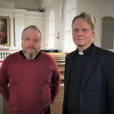 Kaksi miestä seisoo kirkon käytävällä. Oikean puoleinen on mustiin pukeutunut yhtymäjohtaja, vasemmalla punaiseen paitaan pukeutunut pappi. .