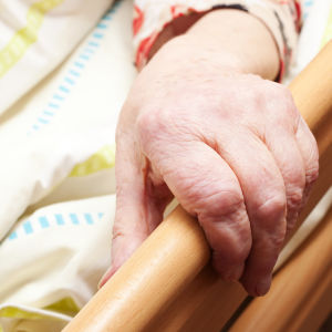 En gammal persons hand håller i ett sängräcke.