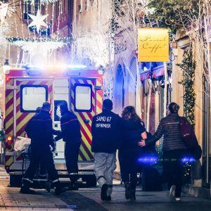 Räddningsarbetare eskorterar en kvinna i det kvarter i Strasbourg där attentatet inleddes.