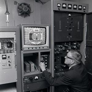 En man justerar radio- och teveteknik.