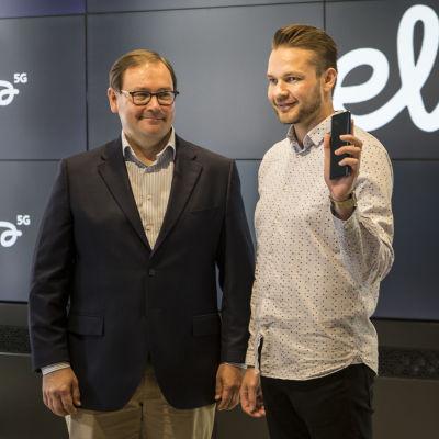 Veli-Matti Mattila, Elisan toimitusjohtaja, antaa ensimmäisen 5G-puhelimen Harri Hellströmille