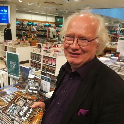 Författaren Stig-Björn Nyberg står bredvid en hög med böcker.
