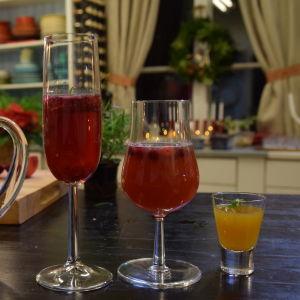 En glaskanna med röd dryck med fruktskivor och bär i, samt ett glas champagne med kall glöggdrink, ett vinglas med tranbärsdryck och ett snapsglas med gul äppelshot.