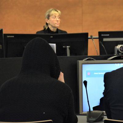 Den åtalade kvinnan fotograferad bakifrån med en uppdragen huva. Bredvid sin man. I bakgrunden syns den kvinnliga tingsrättsdomaren.